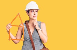 Young beautiful woman wearing architect hardhat holding build project serious face thinking about question with hand on chin, thoughtful about confusing idea