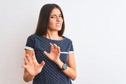 Young beautiful woman wearing blue casual t-shirt standing over isolated white background disgusted expression, displeased and fearful doing disgust face because aversion reaction. With hands raised