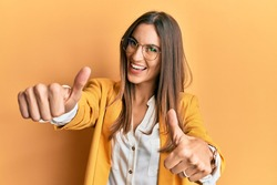 Young beautiful woman wearing business style and glasses approving doing positive gesture with hand, thumbs up smiling and happy for success. winner gesture.