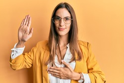 Young beautiful woman wearing business style and glasses swearing with hand on chest and open palm, making a loyalty promise oath