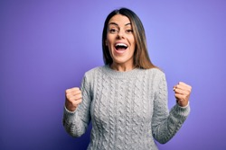 Young beautiful woman wearing casual sweater standing over isolated purple background celebrating surprised and amazed for success with arms raised and open eyes. Winner concept.