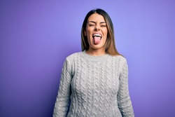 Young beautiful woman wearing casual sweater standing over isolated purple background sticking tongue out happy with funny expression. Emotion concept.