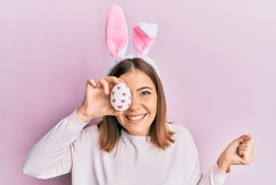 Young beautiful woman wearing cute easter bunny ears holding egg screaming proud, celebrating victory and success very excited with raised arm