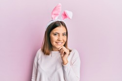 Young beautiful woman wearing cute easter bunny ears looking confident at the camera with smile with crossed arms and hand raised on chin. thinking positive.