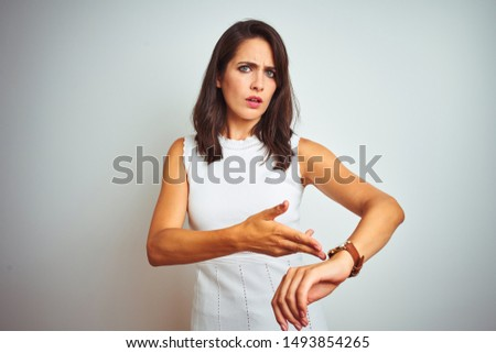 Young beautiful woman wearing dress standing over white isolated background In hurry pointing to watch time, impatience, upset and angry for deadline delay Сток-фото ©