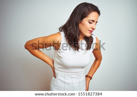 Young beautiful woman wearing dress standing over white isolated background Suffering of backache, touching back with hand, muscular pain