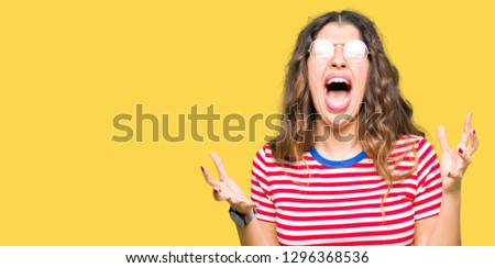 Young beautiful woman wearing glasses crazy and mad shouting and yelling with aggressive expression and arms raised. Frustration concept. Stock fotó ©