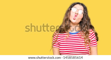 Young beautiful woman wearing glasses making fish face with lips, crazy and comical gesture. Funny expression. #1458585614
