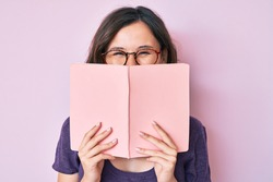 Young beautiful woman wearing glasses reading book smiling and laughing hard out loud because funny crazy joke.