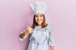 Young beautiful woman wearing professional cook uniform and hat doing happy thumbs up gesture with hand. approving expression looking at the camera showing success.