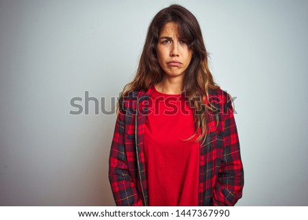 72aa9da4 Young beautiful woman wearing red t-shirt and jacket standing over white  isolated background depressed