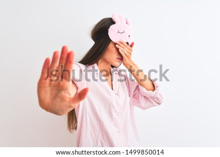 Young beautiful woman wearing sleep mask and pajama over isolated white background covering eyes with hands and doing stop gesture with sad and fear expression. Embarrassed and negative concept.