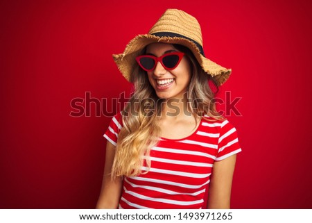 Young beautiful woman wearing sunglasses and summer hat over red isolated background looking away to side with smile on face, natural expression. Laughing confident.