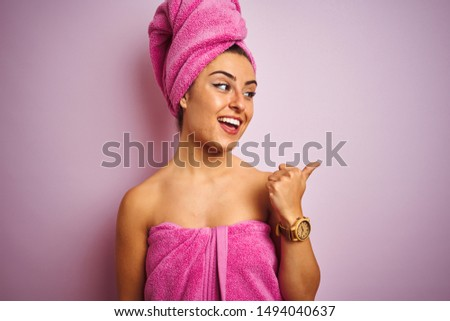 Young beautiful woman wearing towel after shower over isolated pink background smiling with happy face looking and pointing to the side with thumb up. #1494040637