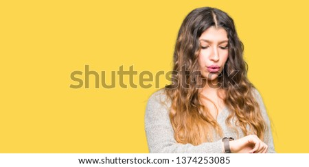 Young beautiful woman wearing winter dress Checking the time on wrist watch, relaxed and confident