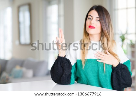 Young beautiful woman wearing winter sweater at home Swearing with hand on chest and fingers, making a loyalty promise oath