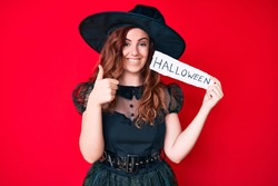 Young beautiful woman wearing witch costume holding paper with halloween message smiling happy and positive, thumb up doing excellent and approval sign