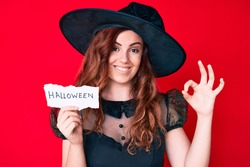 Young beautiful woman wearing witch halloween costume holding paper with halloween message doing ok sign with fingers, smiling friendly gesturing excellent symbol