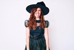 Young beautiful woman wearing witch halloween costume sticking tongue out happy with funny expression. emotion concept.