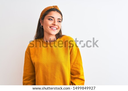 Young beautiful woman wearing yellow sweater and diadem over isolated white background looking away to side with smile on face, natural expression. Laughing confident.