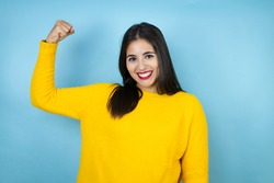 Young beautiful woman wearing yellow sweater over isolated blue background showing arms muscles smiling proud