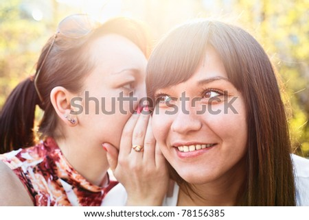 Young beautiful woman whispers something to girlfriend