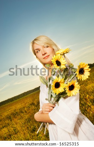 Young beautiful woman with a bouquet of sunflowers in the field