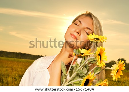 Young beautiful woman with a bouquet of sunflowers in the field at sunset