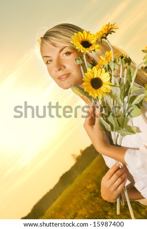 Young beautiful woman with a bouquet of sunflowers in the field at sunset - stock photo