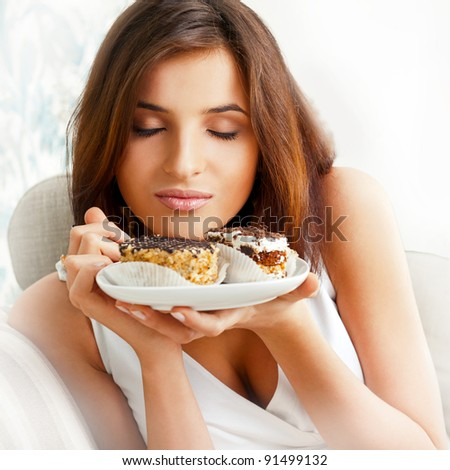 Young beautiful woman with a cake. Closeup portrait. Sitting on sofa at her home