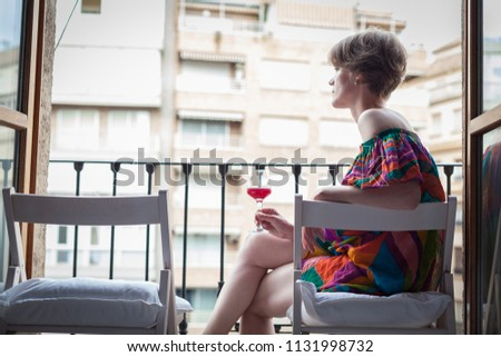 Young beautiful woman with a glass of red wine in hand, on the terrace of the house enjoys the summer sun