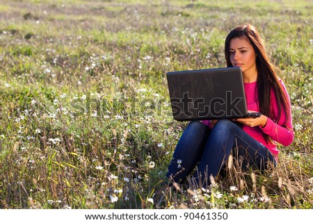 young beautiful woman with a laptop sitting in the field on sky background