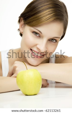 young beautiful woman with an apple looking towards camera