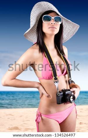 young beautiful woman with bikini holding vintage retro camera