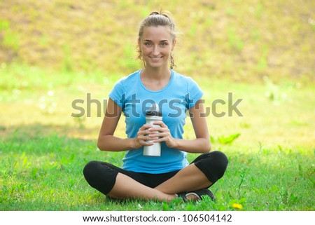Young beautiful woman with bottle of water after fitness exercise outdoors