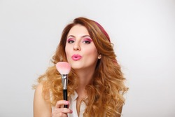 Young beautiful woman with bright pink make up and curly red hair blows off powder or blush from the makeup brush on grey background at studio. Visagiste, makeup artist.