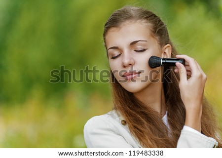 Young beautiful woman with closed eyes causes powder to face, against background of autumn park.