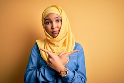 Young beautiful woman with curly hair wearing arab traditional hijab over yellow background Pointing to both sides with fingers, different direction disagree