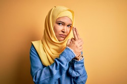Young beautiful woman with curly hair wearing arab traditional hijab over yellow background Holding symbolic gun with hand gesture, playing killing shooting weapons, angry face
