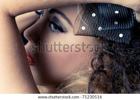 Young beautiful woman with dark eye makeup, closeup studio portrait
