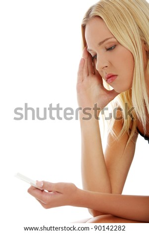 Young beautiful woman with depression holding pregnancy test