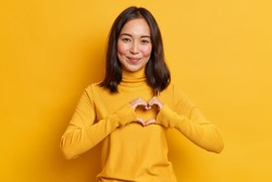 Young beautiful woman with eastern appearance shapes heart gesture over chest confesses in love and admiration smiles gently wears casual turtleneck isolated over vivid yellow studio background.