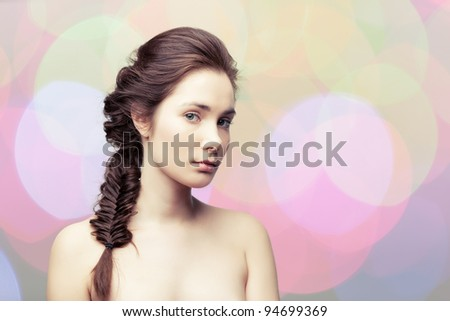 Young beautiful woman  with elegant hairdo on colorful pastel background