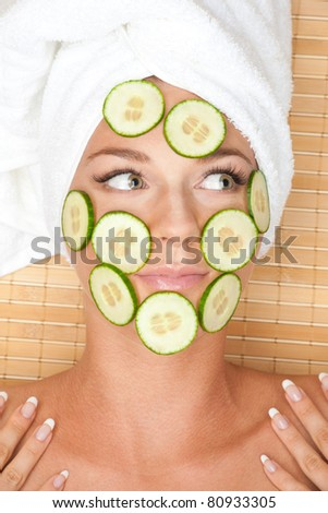 Young beautiful woman with facial mask of cucumber on her face lying at spa salon