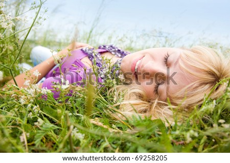 young beautiful woman with fair hair lying and  enjoy on the meadow