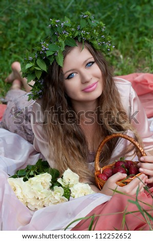 Young beautiful woman with flower wreath and strawberry laying in meadow at summer