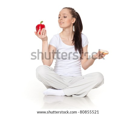 Young beautiful woman with fresh pepper and doughnut on a white background. Concept of healthy food.