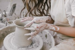 Young beautiful woman with long curly hair in white apron creating handmade ceramic bowl in a pottery. Creative workshop.