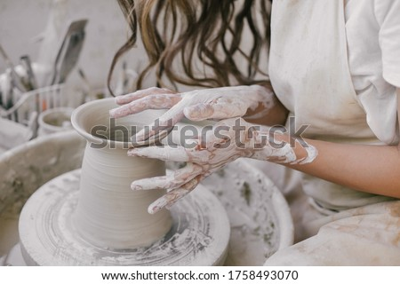 Young beautiful woman with long curly hair in white apron creating handmade ceramic bowl in a pottery. Creative workshop. Сток-фото ©