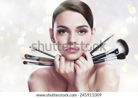 Young beautiful woman with makeup brushes near her face, skin care concept / photoset of attractive brunette girl on blurred background with bokeh